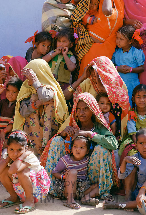 Group of Indian women wearing traditional saree and watching festivities with their children, India