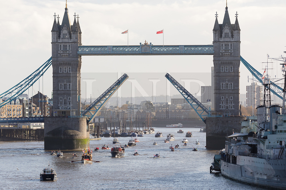 © Licensed to London News Pictures. 11/11/2018. London, UK.  A flotilla of boats including the Royal barge, QRB Gloriana, the Havengore and traditional boats travel up the River Thames as Tower Bridge lifts in salute, towards the Houses of Parliament in Westminster for a remembrance service, led by the Havengore, as part of Armistice Day centenary events taking place in central London. Big Ben will strike at 11am to mark the start of the two minutes silence and the Havengore will sound her horn to signify the end of the two minutes silence in central London.  Photo credit: Vickie Flores/LNP