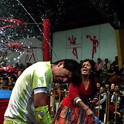 Yolanda La Amorosa throws water over her male counterpart as they fight out of the ring during the 'Titans of the Ring' wrestling group's Sunday performance at El Alto's Multifunctional Centre. Bolivia. The wrestling group includes the fighting Cholitas, a group of Indigenous Female Lucha Libra wrestlers who fight the men as well as each other for just a few dollars appearance money. El Alto, Bolivia, 14th March 2010. Photo Tim Clayton