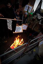 © under license to London News Pictures. 11/11/2010. Muslims Against Crusaders protesters burn a poppy, during the two-minute silence, on Exhibition Road in London at 11am on Armistice Day.