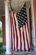 American flag on the porch of a home ruined by  Katrina n New Orleans a year and a half after the storm.
