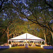 A wedding reception is seen under a tent at dusk at the Legare Waring House & Gardens at Charles Towne Landing in Charleston.©Travis Bell Photography
