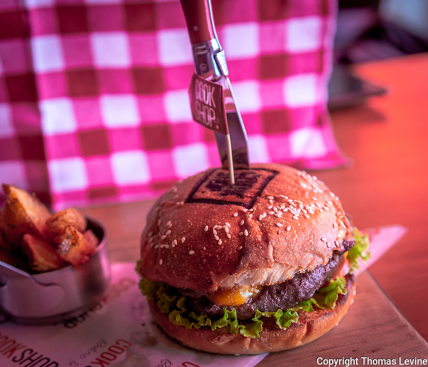 Cheeseburger on a brown bun with lettuce and cheddar cheese in Asia. Available almost anywhere in the world as International Food. RAW to Jpg