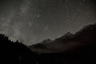 The Milky Way and stars fill a dark sky and clouds swirl among mountains near Valdez, Alaska