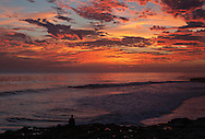 Man watching the sunset and surfers, West Cliff Drive, Santa Cruz, California