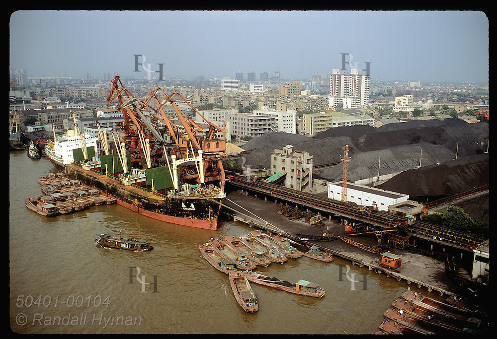 Barges and ocean freighter dock along a coalyard on banks of the Huangpu River in Shanghai. China
