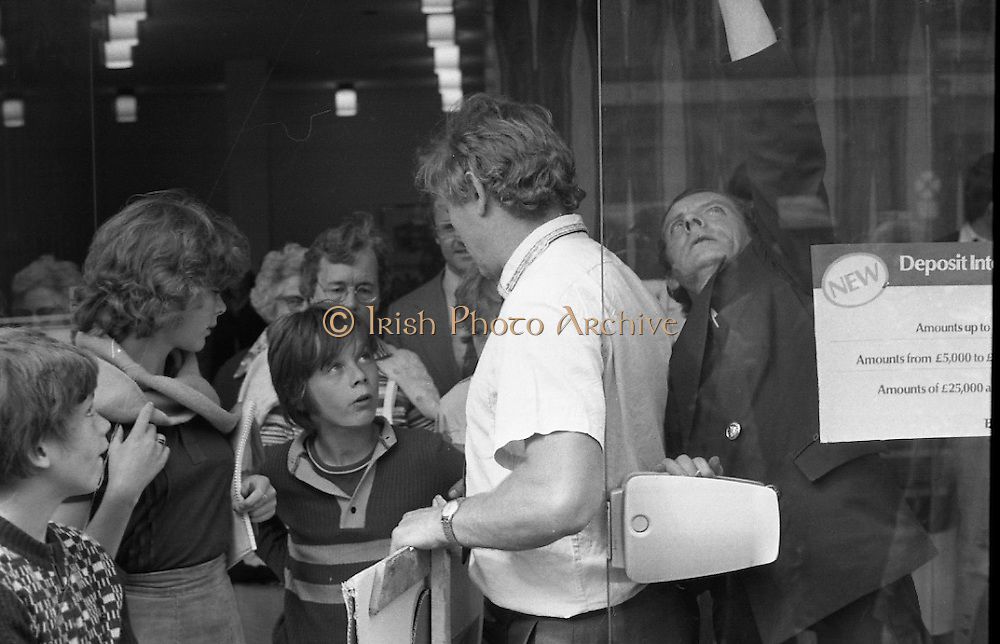 Fergus Rowan sits in at Bank of Ireland.  (J70)..1975..22.08.1975..08.22.1975..22nd August 1975..As a result of the 1970 bank strike which lasted for six months, the Rowan family business found itself in financial difficulties. During the strike the Rowans had had to accept cheques in good faith in order to stay in business. When the cheques came for settlement the bank refused as they stated that some were 'dodgy'. This put severe strain on the business which was eventually put into receivership.As part of the process the Rowan business beside the bank was put up for sale and was purchased by B.o I. Rowan was outraged and started a campaign against the bank which culminated in a sit in at the banks headquarters in Westmoreland St,Dublin. He also became a thorn in the side of the bank at the A.G.Ms raising many points...Image shows Mr Rowan discussing the High Court order with his family.