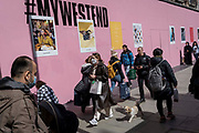 On the day that the UK government eased Covid restrictions to allow non-essential businesses such as shops, pubs, bars, gyms and hairdressers to re-open, shoppers pass an Oxford Street hoarding advertising the West End hashtag, on 12th April 2021, in London, England.