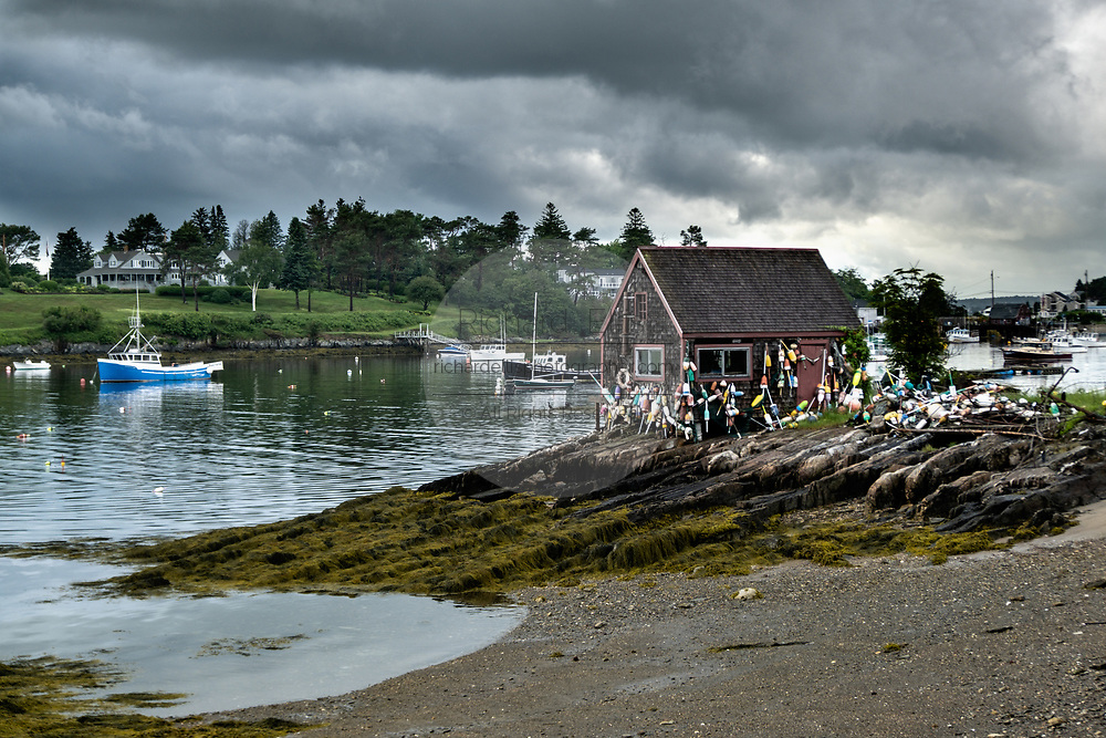 Historic Bailey Fish House covered in lobster buoys along Mackerel Cove on Bailey Island on a stormy summers day in Harpswell, Maine.