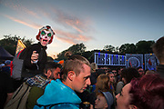 Boy with clown face paint in the Shangri La field, Glastonbury Festival 2016.  The Glastonbury Festival is the largest greenfield festival in the world, and is now attended by around 175,000 people. Its a five-day music festival that takes place near Pilton, Somerset, United Kingdom. In addition to contemporary music, the festival hosts dance, comedy, theatre, circus, cabaret, and other arts. Held at Worthy Farm in Pilton, leading pop and rock artists have headlined, alongside thousands of others appearing on smaller stages and performance areas.