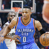 21 December 2015: Oklahoma City Thunder guard Russell Westbrook (0) drives past Los Angeles Clippers guard Chris Paul (3) on a screen set by Oklahoma City Thunder center Steven Adams (12) during the Oklahoma City Thunder 100-99 victory over the Los Angeles Clippers, at the Staples Center, Los Angeles, California, USA.
