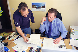 Man with disability discussing document with colleague in office,