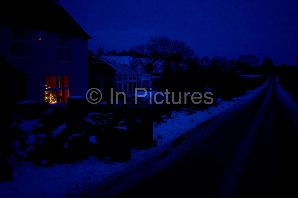 A Christmas tree glows in a warm window of a rural house seen from outside in bleak temperatures during mid-winter snows in England. In deep blue light we experience from the feel of this picture, the rawness of deep winter, the icy conditions where an unseen country-living family are safe indoors. The property is a cottage on a quiet road in the Mendip hills, southeast of the city of Bristol in western England. It is during the Christmas holiday period and families, who are lucky to have reached their homes during very difficult weather, are now enjoying the solitude and tranquillity of a peaceful life - away from the metropolis. Their brick wall is topped with snow and the light from the burglar alarm shows the security system is active. We also see the bleak landscape of bare trees and the remote icy road.