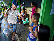 """20 JANUARY 2018 - CAMALIG, ALBAY, PHILIPPINES: A """"taho"""" vender (a sort of Filipino custard made with tofu) sells the snack to evacuees at the Barangay Cabangan evacuee shelter in a school in Camalig. There are about 650 people living at the shelter. They won't be allowed to move back to their homes until officials determine that Mayon volcano is safe and not likely to erupt. More than 30,000 people have been evacuated from communities on the near the Mayon volcano in Albay province in the Philippines. Most of the evacuees are staying at school in communities outside of the evacuation zone.  PHOTO BY JACK KURTZ"""