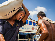 22 OCTOBER 2015 - YANGON, MYANMAR: Men unload rice from barges that sail up and down the Yangon River and other rivers in Myanmar.    PHOTO BY JACK KURTZ