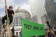 London, UK. Thursday 14th June 2013. Anti G8 demonstrators on tripods in the Canary Wharf business district of London. Part of a protest called 'They Owe Us' whose point is that while rich G8 countries meet, it is the pooor who are still paying.