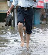 Man running in a flooded street during the monsoon season, Cochin, Kerala, India