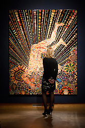 © Licensed to London News Pictures. 05/10/2012. LONDON, UK. A member of Christie's staff looks at Fred Tomaselli's 'ORGAMISM' [sic] (2005) estimated to fetch GB£400,000-600,000 at an auction preview in London today (05/10/12)The evening auction, consisting of pieces of Italian art, takes place at Christie's St James' auction house on the 11 October 2012. Photo credit: Matt Cetti-Roberts/LNP