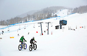 SHOT 2/9/13 4:06:14 PM - A pair of fat tire bikers climb the hill at Vail's Golden Peak while warming up before the On-Snow Bike Crit event at the second annual Winter Mountain Games presented by Eddie Bauer at Vail Ski Resort in Vail, Co. The Winter Mountain Games feature competitions in X-Country On-Snow Mountain Bike Races, mixed climbing, Telemark Big Air, Best Trick Bike and On-Snow Mountain Bike Crit with more than $60,000 in prize money on the line. (Photo by Marc Piscotty / © 2013)