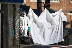 A forensics investigator collapses the police tent where a man alleged by witnesses to be a drug dealer was stabbed to death outside Ilford Station following a fight outside a Paddy Power betting shop 100 yards away on Ilford High Road. London, February 27 2019.