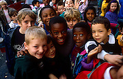 Schoolchildren of many ages and ethnic backgrounds spend their morning break-time in their school playground in inner-city London. Faces of a variety of skin colours and expressions look to the viewer as the kids delight in having their picture taken. Their cheeky, mischievous grins make us smile as we remember our own pre-technology childhoods, an era before computers took our natural sense of outdoor fun away.