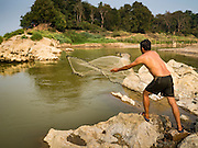 11 MARCH 2016 - LUANG PRABANG, LAOS:   A man does subsistence fishing in the Nam Khan River near its confluence with the Mekong River in Luang Prabang, Laos. Laos is one of the poorest countries in Southeast Asia. Tourism and hydroelectric dams along the rivers that run through the country are driving the legal economy.     PHOTO BY JACK KURTZ