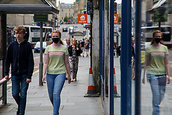 © Licensed to London News Pictures. 14/07/2021. Edinburgh, Scotland, UK. A woman wearing a face covering  in Edinburgh on a warm and sunny day. According to the Met Office, a high of 23 degrees celsius is forecast for the rest of the week. Scotland's first minister, Nicola Sturgeon has said that Scotland will move to a 'modified' form of level 0 on 19 July and wearing of face coverings will remain mandatory. Photo credit: Dinendra Haria/LNP