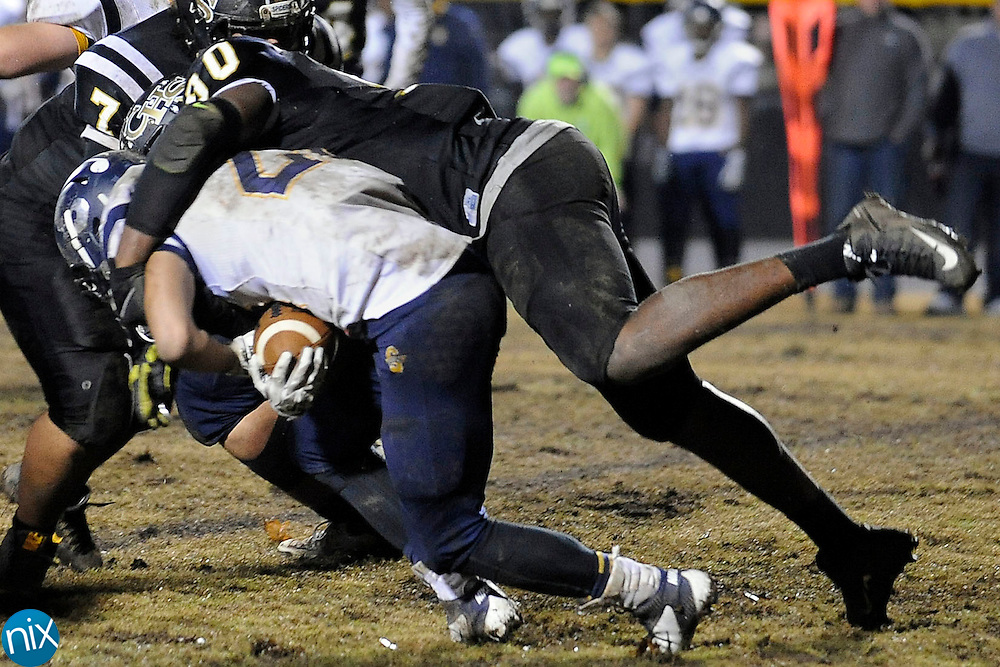 Spiders defensive end Rick Sandidge (90, top) hits Vikings running back Tyree Hallman (22) in the second half  of the South Iredell Vikings at Concord Spiders 3A high school football playoff game on Nov. 27.