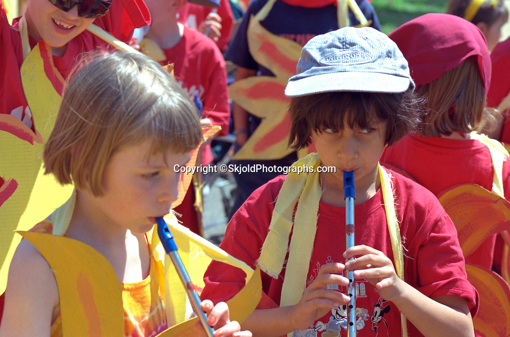 Girls age 7 playing recorders. In the Heart of the Beast May Day Festival and Parade St Paul  Minnesota USA