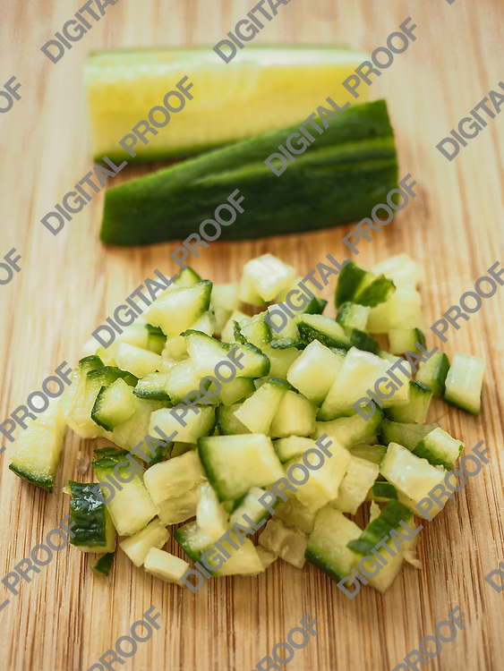 Cucumber cutted in dices over a wood table with rest of cucumber at background - frontal view