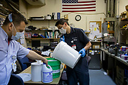 Maintenance mechanic Roy Carrera pours water and bleach over paper towels to make sanitizing wipes Thursday, May 14, 2020 as the staff does each morning in the workshop at St. Anthony Hospital. (Brian Cassella/Chicago Tribune)