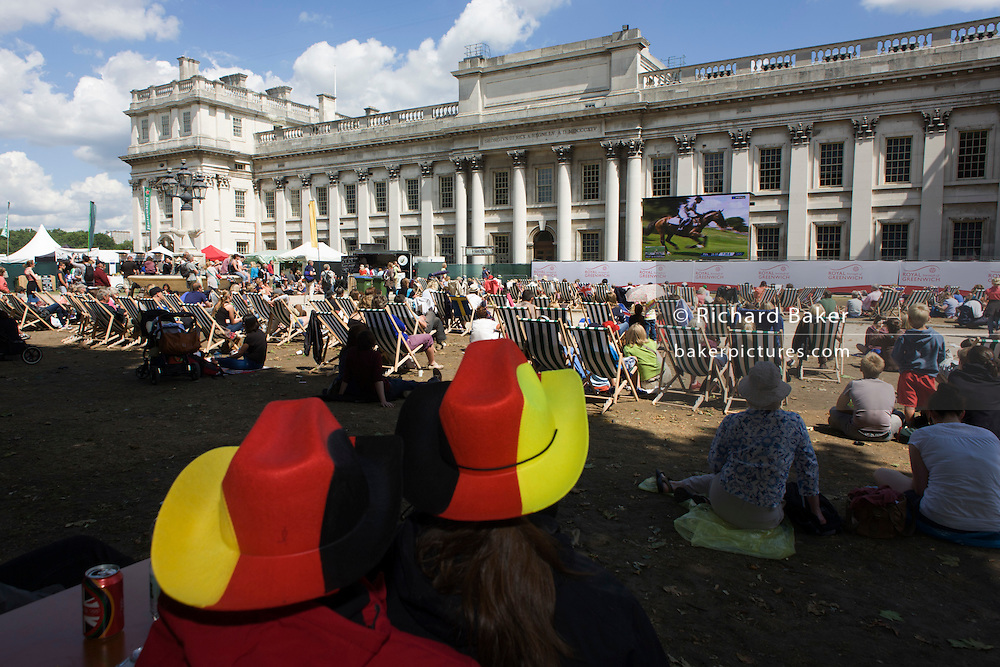 Watching live TV coverage of Equestrian events, German spectators and other sports fans sit in summer deckchairs at the old Royal Naval College, Greenwich on day 4 of the London 2012 Olympic Games. Greenwich Park is hosting the Olympic Equestrian competitions, plus the combined running and shooting event of the Modern Pentathlon. The Old Royal Naval College is the architectural centrepiece of Maritime Greenwich, a World Heritage Site in Greenwich, London. The buildings were originally constructed to serve as the Royal Hospital for Seamen at Greenwich, now generally known as Greenwich Hospital, which was designed by Christopher Wren, and built between 1696 and 1712.