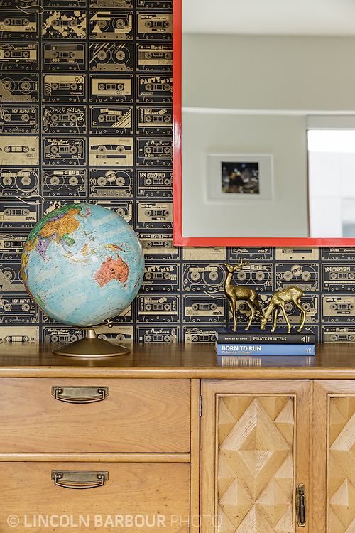 Hip wallpaper with a cassette tape pattern, a globe, and gold deer decorate this detail credenza shot.