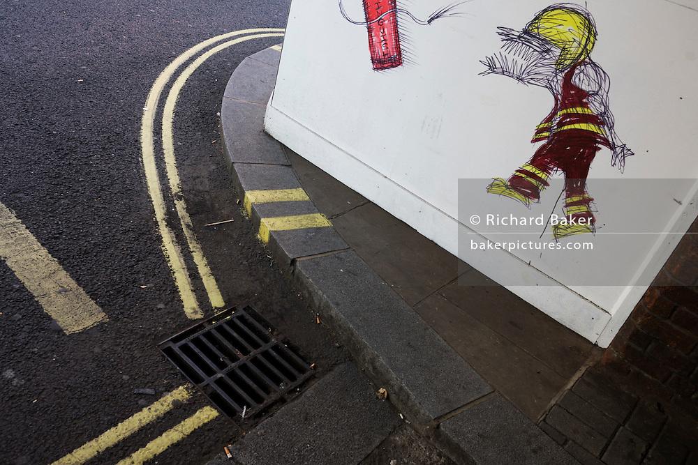 Cartoon graffiti by street artist Nathan Bowen of fireman created outside a London fire station.