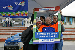Wednesday 8th May 2019.<br /> Sinenjongo High School, Joe Slovo Park,<br /> Milnerton, Cape Town, <br /> Western Cape, <br /> South Africa.<br /> <br /> SOUTH AFRICAN GENERAL ELECTIONS 2019!<br /> <br /> SOUTH AFRICAN PROVINCIAL AND NATIONAL ELECTIONS 2019! <br /> <br /> Smiling DA political party members hold up a DA poster cut out frame as they stand at their representatives table outside the voting station at Sinenjongo High School, Joe Slovo Park near Milnerton, Cape Town, Western Cape, South Africa.  <br /> <br /> Registered South African Voters head to the various IEC (Independent Electoral Commission) Voting Stations where they are registered to vote as they cast their votes and take part in voting and other activities on Voting Day 8th May 2019 during the South African General Elections 2019. Voters from across the nation stood in queue's along with many others to vote in the Provincial and National Elections being held in South Africa on Wednesday 8th May 2019.   <br />  <br /> Copyright © Mark Wessels. All Rights Reserved. No Usage Without Permission.<br /> <br /> PICTURE: MARK WESSELS. 08/05/2019.<br /> +27 (0)61 547 2729.<br /> mark@sevenbang.com<br /> studioseven@mweb.co.za<br /> www.markwesselsphoto.com