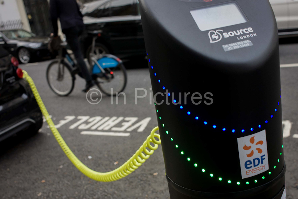 A cyclist passes a parked Smart car recharges electric power at an EDF charging point in central London. Its yellow coiled cable stretching from charging point to car. Source London is now the capital's largest charging network. It has significantly boosted existing numbers of charge points operated by a range of different localised schemes. By 2013, Source London will total at least 1,300 charge points, more than the number of petrol stations currently in London, ensuring the infrastructure is in place for significantly more people and businesses to buy an electric vehicle. The creation of an electric vehicle network is in line with the Mayor's pledge to promote quality of life by reducing pollution and CO2 emissions.