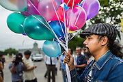 """24 JUNE 2014 - BANGKOK, THAILAND: Members of the """"Monsoon Poets Society"""" carry helium balloons in front of the Anantasamakom Throne Hall Tuesday to pay homage to the People's Party, a Siamese (Thai) group of military and civil officers (which became a political party) that staged a bloodless coup against King Prajadhipok (Rama VII) and changed Thailand (then Siam) from an absolute monarchy to a constitutional monarchy on 24 June 1932. Since the coup against the civilian government on 22 May, the ruling junta has not allowed political gatherings. Although police read the poems, they did not arrest any of the poets or make any effort to break up the gathering.     PHOTO BY JACK KURTZ"""