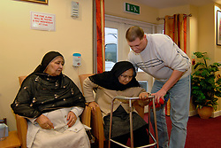 A Care Assistant helps an elderly Asian lady up out of her chair in a day centre; Bradford,