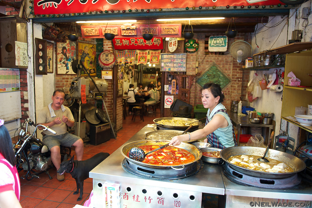 A woman stirs several types of tofu dishes on Shenkeng Old Street, near Taipei, Taiwan.