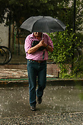 People rush to take cover during a heavy rain in capital Tirana as electoral campaign rallies continue ahead of the upcoming general election in Tirana, Albania on Monday, June 22, 2009. Albanians will vote in the legislative elections on 28 June. (Photo by Vudi Xhymshiti)