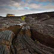 The warm sunset colors of clouds offset with the lines and textures of hardened lava with house perched on a hill in Hawaii Volcanoes National Park.