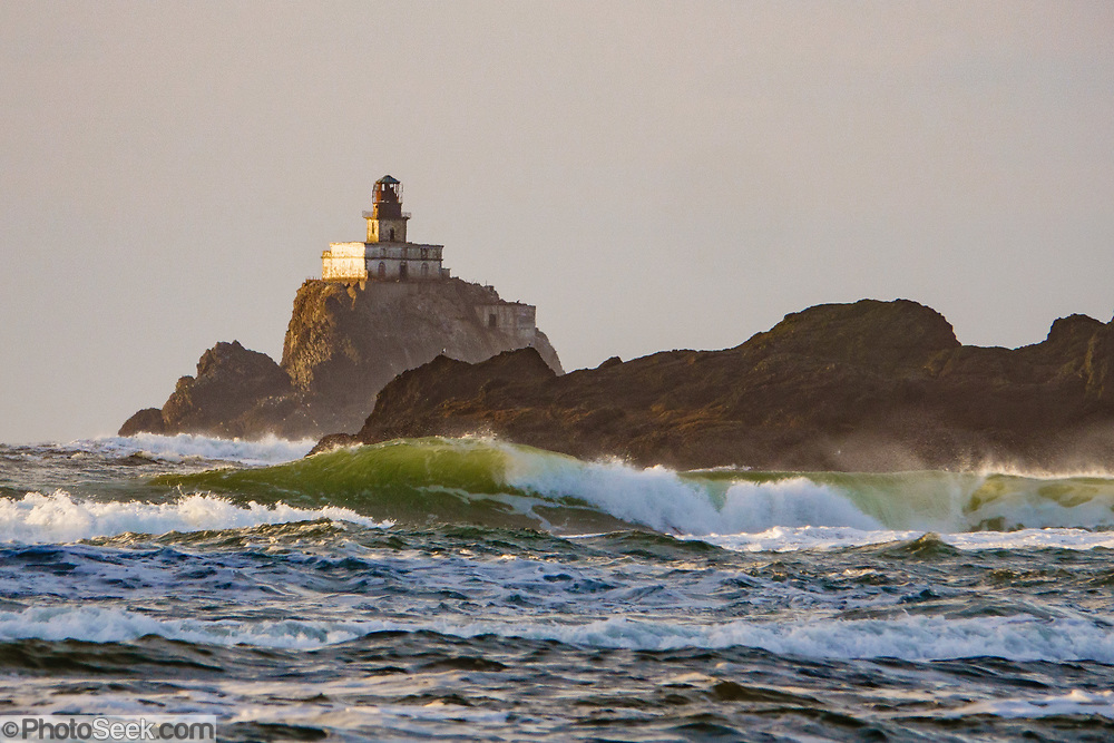 Tillamook Lighthouse clings to a sea stack amid crashing waves, seen from Chapman Beach. Cannon Beach city, Oregon coast, USA.