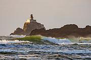Tillamook Lighthouse clings to a sea stack amid crashing waves, seen from Chapman Beach. Cannon Beach city, Oregon coast, USA.