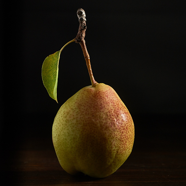 Organic pear on a black background with dramatic light.