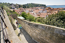 Biker climbing up on paved surface by stone wall with houses in background