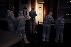 © Licensed to London News Pictures . 22/11/2013 . Manchester , UK . Forensic examiners use torchlight outside the house as darkness falls . Police and forensic scenes of crime investigators on the scene at 18 Mayford Road , Levenshulme , where the body of a 49 year old mother of four , Aisha Alam , was discovered stabbed to death today (Friday 22nd November 2013) after a man , understood to be Aisha's husband , walked in to Longsight Police Station to report she had been killed . Photo credit : Joel Goodman/LNP