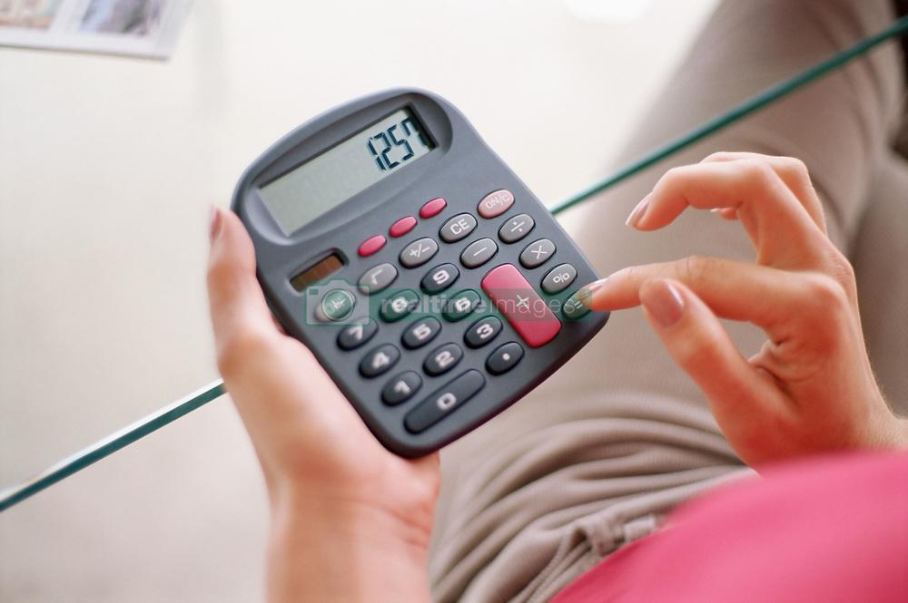 Dec. 14, 2012 - Woman using calculator (Credit Image: © Image Source/ZUMAPRESS.com)