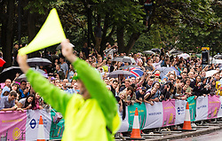 © Licensed to London News Pictures. 07/07/2014. London, UK. A marshal waves a flag near Tower Bridge ahead of the Tour de France stage 3 in London. Photo credit : Vickie Flores/LNP