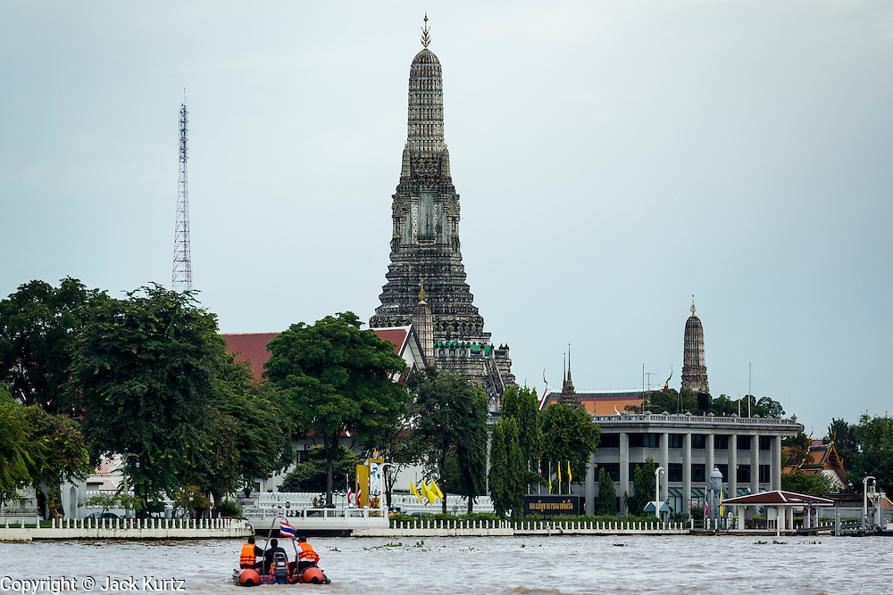 """23 SEPTEMBER 2013 - BANGKOK, THAILAND:  Wat Arun, on the west bank of the Chao Phraya River, in Bangkok. The full name of the temple is Wat Arunratchawararam Ratchaworamahavihara. The outstanding feature of Wat Arun is its central prang (Khmer-style tower). The world-famous stupa, known locally as Phra Prang Wat Arun, will be closed for three years to undergo repairs and renovation along with other structures in the temple compound. This will be the biggest repair and renovation work on the stupa in the last 14 years. In the past, even while large-scale work was being done, the stupa used to remain open to tourists. It may be named """"Temple of the Dawn"""" because the first light of morning reflects off the surface of the temple with a pearly iridescence. The height is reported by different sources as between 66,80 meters and 86 meters. The corners are marked by 4 smaller satellite prangs. The temple was built in the days of Thailand's ancient capital of Ayutthaya and originally known as Wat Makok (The Olive Temple). King Rama IV gave the temple the present name Wat Arunratchawararam. Wat Arun officially ordained its first westerner, an American, in 2005. The central prang symbolizes Mount Meru of the Indian cosmology. The temple's distinctive silhouette is the logo of the Tourism Authority of Thailand.          PHOTO BY JACK KURTZ"""
