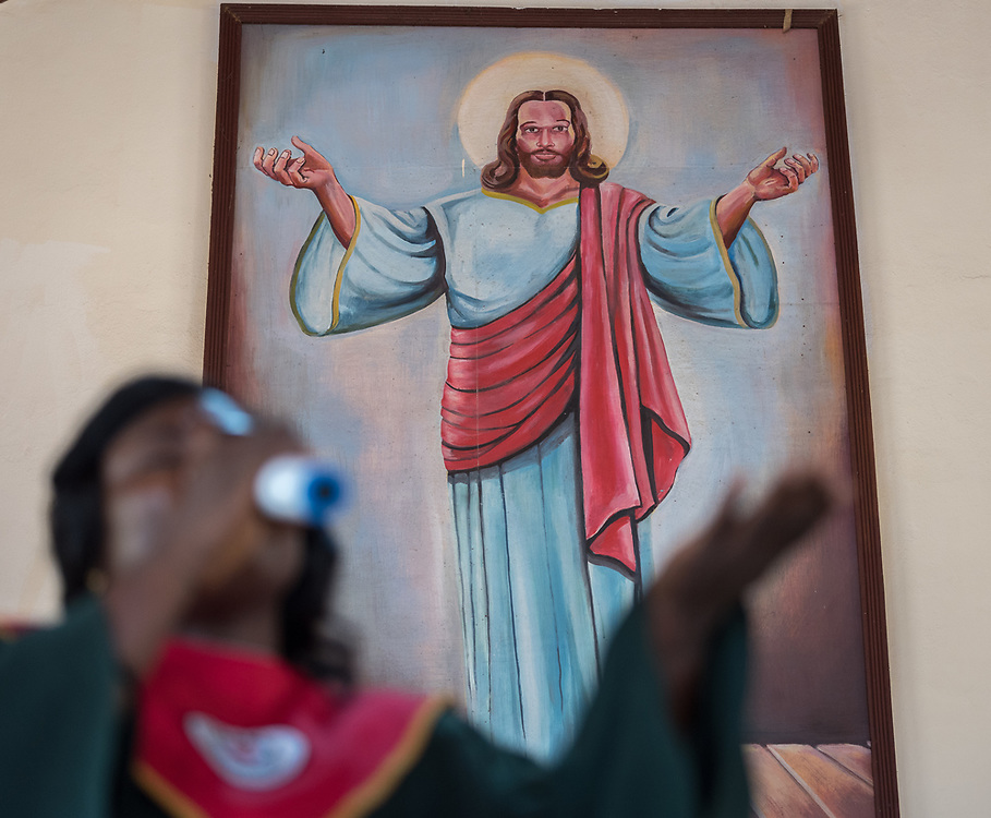 3 November 2019, Monrovia, Liberia: A woman sings in front of an image of Jesus during Sunday service at Saint Andrew Lutheran Parish in Monrovia. Part of the Lutheran Church in Liberia, the parish gathers some 220 members for prayer each week.